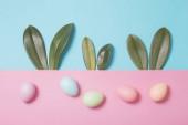 Hasenohren aus grünen Blättern und bemalten Eiern auf Kleister