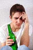 Fotografie Trauriger junger Mann mit einem Bier
