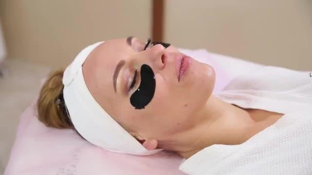 Hand eines professionellen Kosmetikers, der Goldmaske auf das Gesicht des Kunden aufträgt.