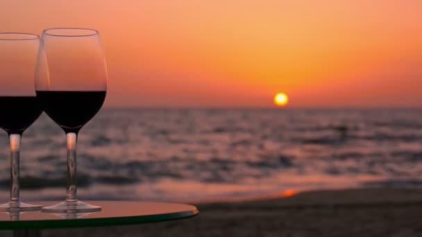 Sklenice vína na stole proti moři