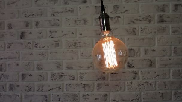 Lampada Loft dellannata che oscilla su un fondo del muro di mattoni