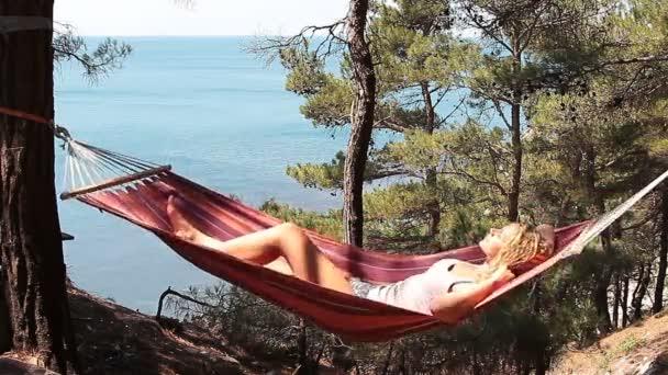 Krásná mladá dívka odpočívá v houpací síti