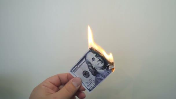 Ruce drží hořící stodolarových bankovek