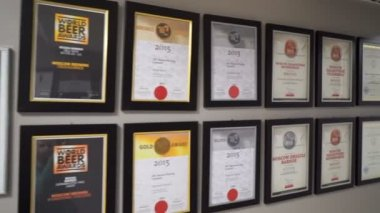 Diplomas and awards in the framework hang on the wall