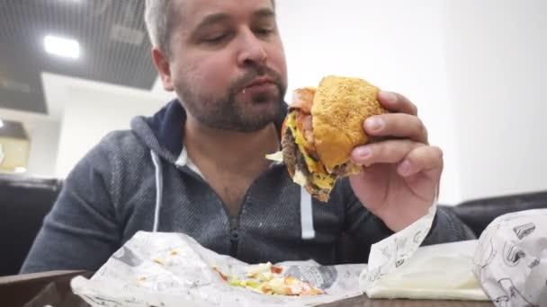 Hungry man eating big hamburger in fast food cafe