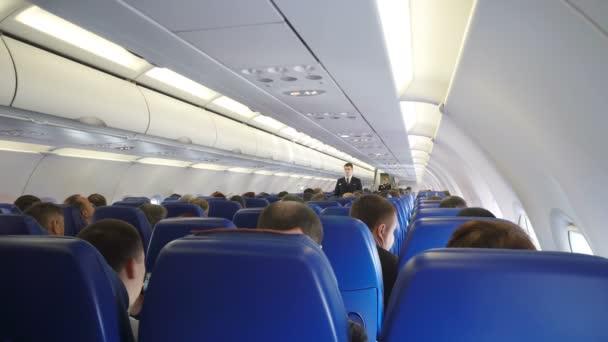 Moskva, Ruská federace 16. března 2017: Interiér letadla s cestujícími na sedadlech a stevard provádí bezpečnostní výcvik po startu.
