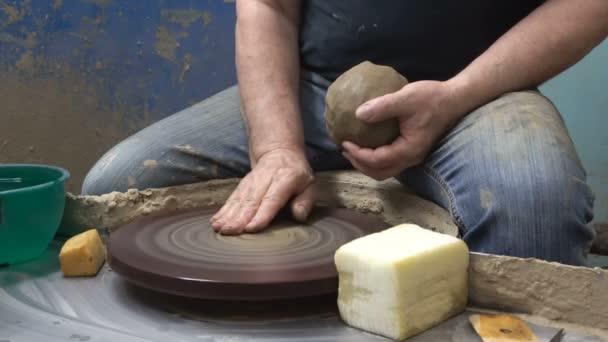 Nahaufnahme der Hand eines Töpfers modelliert einen Topfkrug aus Ton auf einer Töpferscheibe
