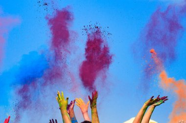 At the color Holi Festival, hands in the air, blue sky behind stock vector