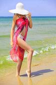 Nő nagy szalma széles karimájú kalap és piros Pareo (pareó) egy homokos strandjával. Nyári üdülés koncepció