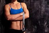 Fotografia Donna fitness forte con una misura di nastro su sfondo scuro