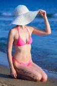 Žena ve velkých slaměný klobouk opalování na písečné pláži. Letní prázdniny koncept