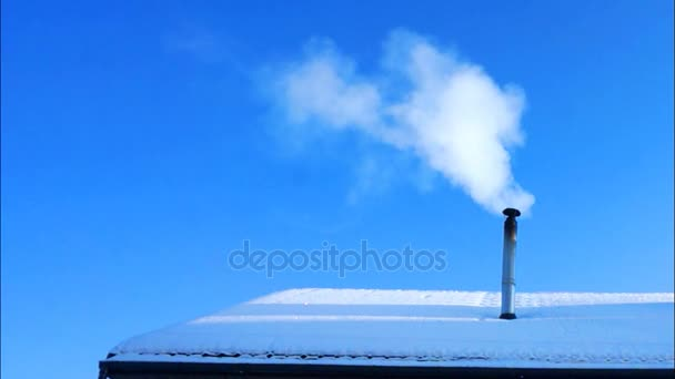 Smoke from the chimney on snowcovered house