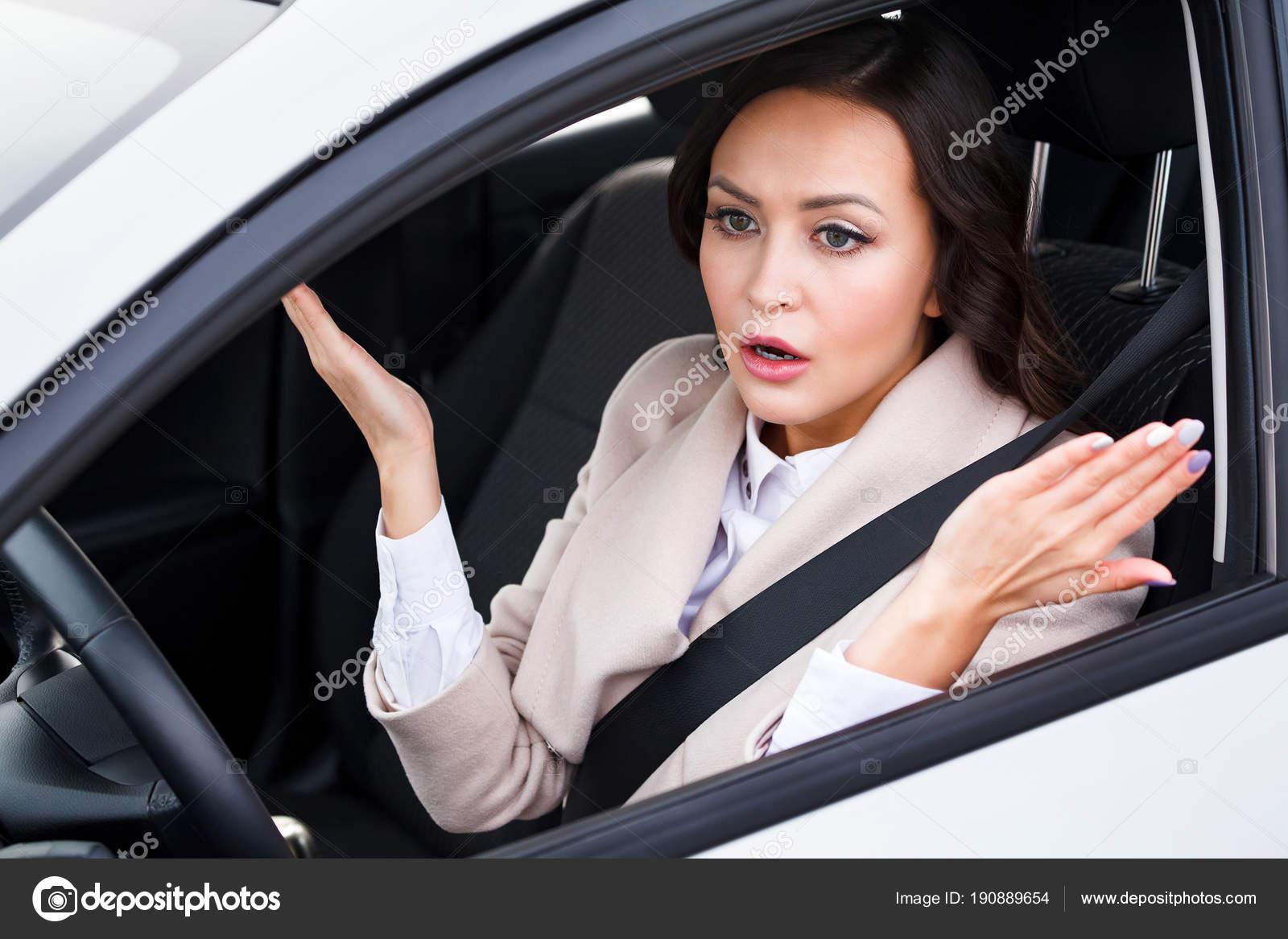 pilote de jeune jolie femme conduire une voiture et de discuter avec quelqu 39 un photographie. Black Bedroom Furniture Sets. Home Design Ideas