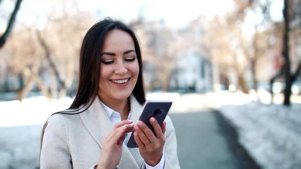 Hübsche Frau benutzt ihr Smartphone im Freien