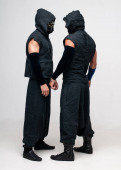 Two dancers dressed in black robes and masks