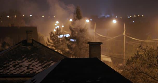 Střechy a komíny v noci kouří na ulici
