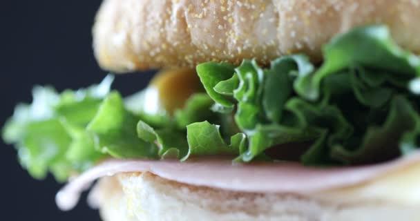 Sendvič na černém pozadí. Detailní záběr na rotující sendvič.