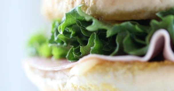 Sendvič na bílém pozadí. Detailní záběr na rotující sendvič