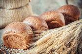 Čerstvý chléb buchty, uši pšenice a pytlík mouky.