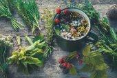 Zdravý bylinkový čaj v Černošcích léčivých bylin a smaltovaných hrnek. Bylinné medicíny. Retro tónovaný.