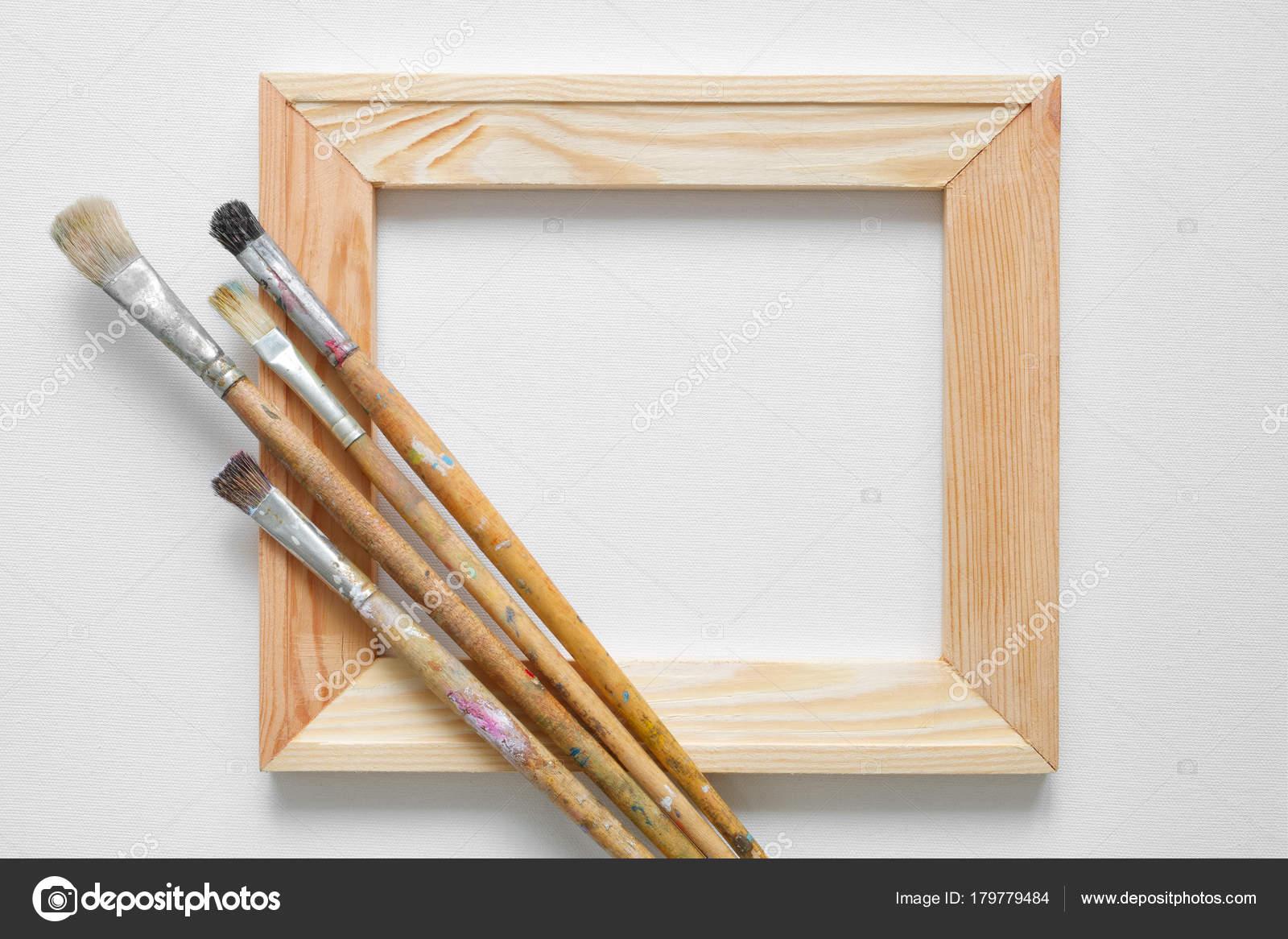Barra de madera camilla y pinceles de artista blanco de lona fondo ...