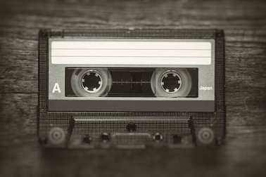Retro stylized photo of vintage Audio cassette tape with blur and noise effect.