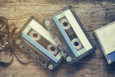 Two vintage audio cassette tapes on wooden background.