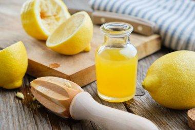 Lemon juice or oil bottle, wooden juicer and lemon citrus fruits