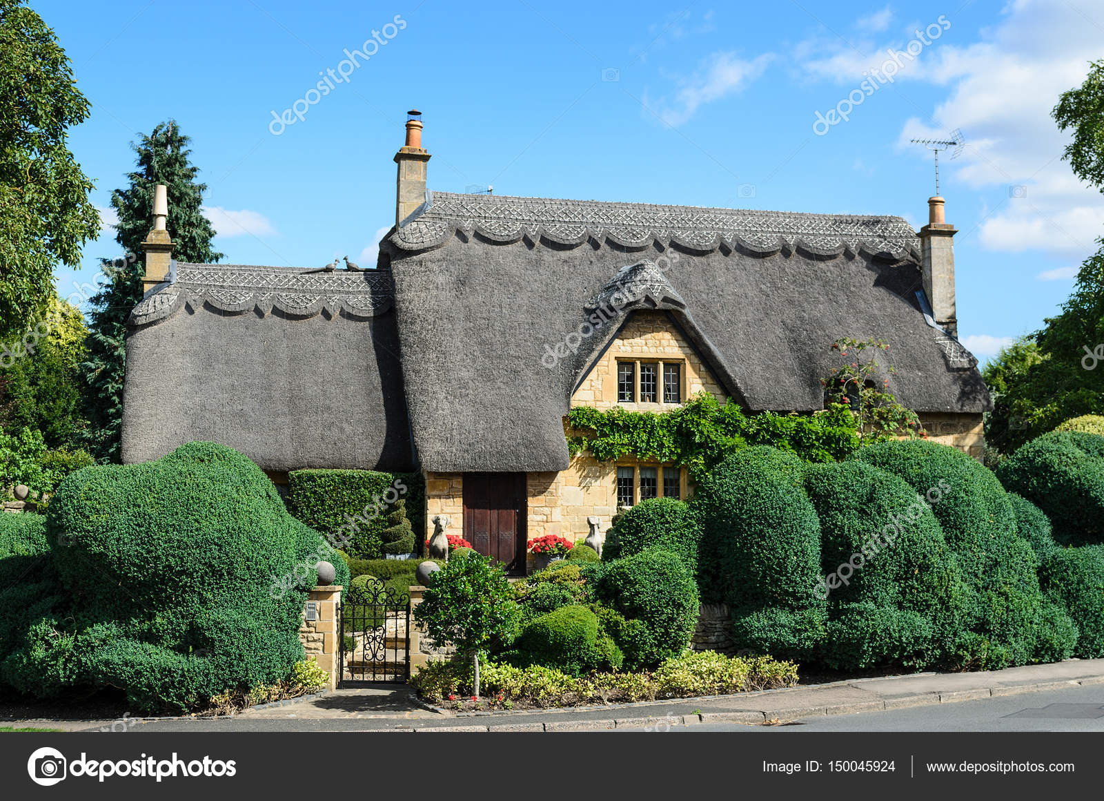 An English Thatched Cottage Built Out Of Cotswold Stone With A Beautiful Hedge In The Garden Chipping Campden Cotswolds England UK