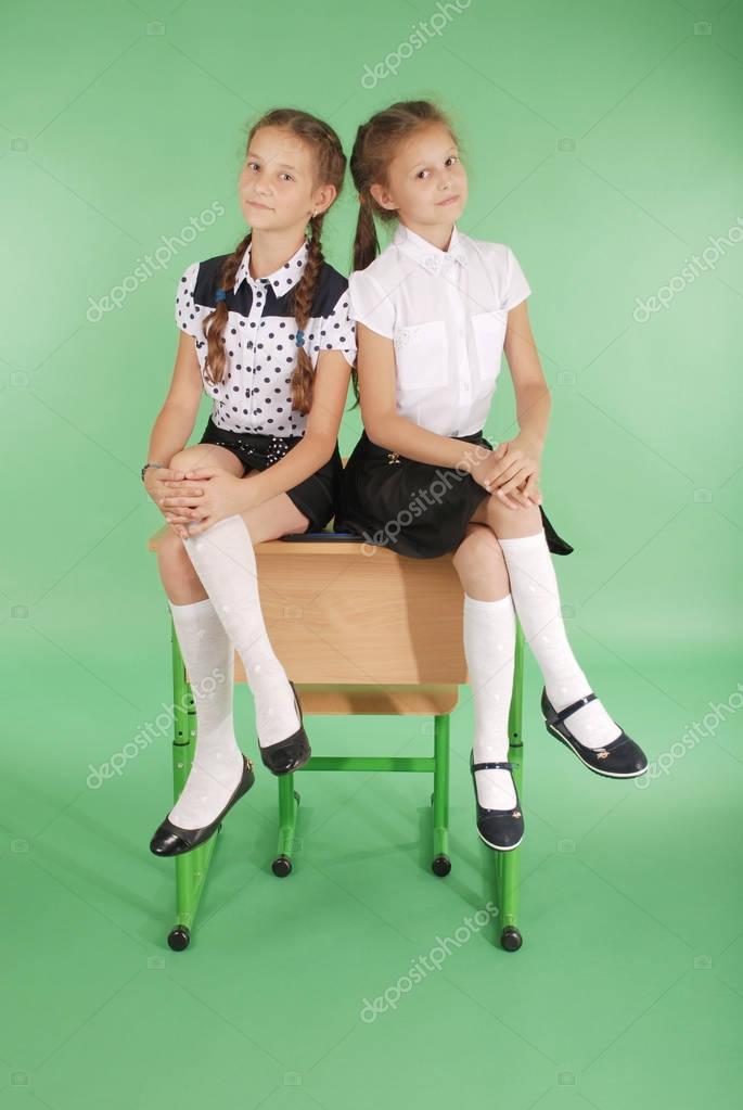 c217d74d8 Dos niñas en uniforme escolar sentado en el escritorio — Fotos de Stock