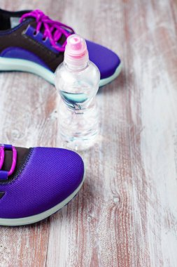 sport shoes and water on a wooden background