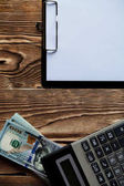 notepad , money and black calculator on wood table wit copy space