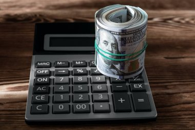 money and black calculator on wood table wit copy space