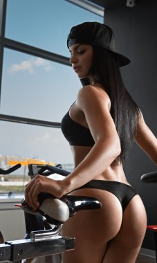 Portrait of young woman wearing sport bra and using a exercise bike at the gym