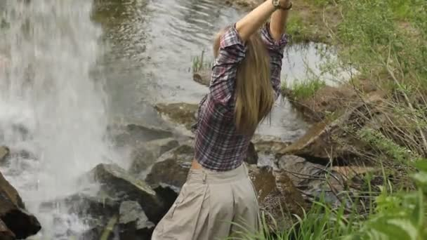 mladá žena relaxovat a otevřenou náručí k vodopádu