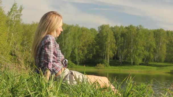 Woman relaxes by the lake shore sitting on the green grass. Summer holidays concept.