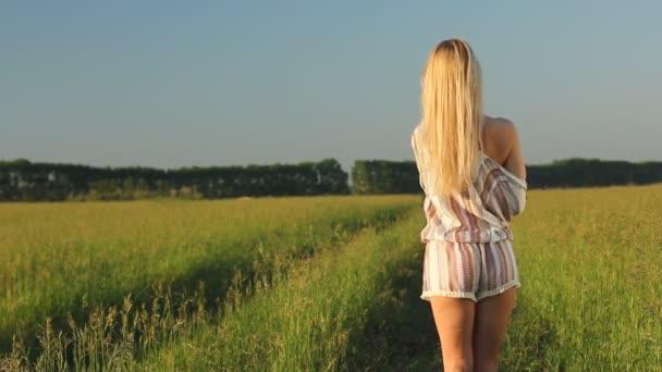 Dívka v boho stylu oblečení svléká pokojně na venkovské silnici v zeleném poli slunečného letního večera