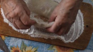 Grandmother's hands. Female hands do flat cakes. Top view.