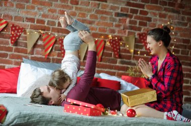 Young family gleefully congratulates each other Marry Christmas