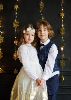 Christmas. Two festively dressed children, boy and girl, are holding hands.