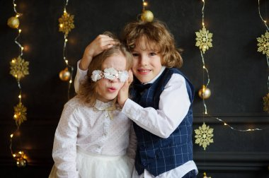 Two festively dressed children photographed for Christmas card.