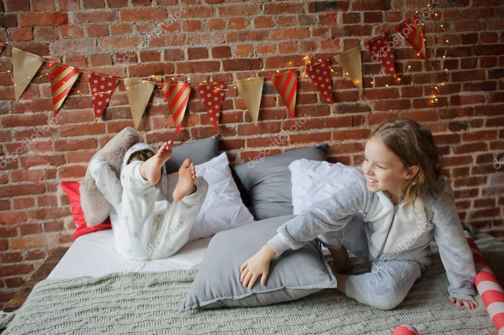Twee kinderen in pyjama van zachte hebben gerangschikt kussens