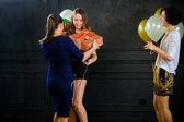 Dívka přijímá gratulace a dary od kamarádky