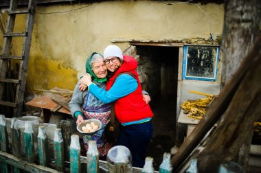 The young woman embraces the old woman.