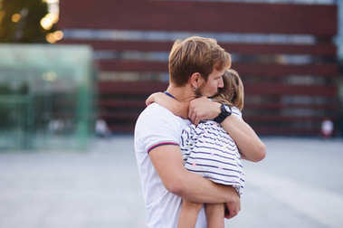 Young father holds the little daughter on hands.