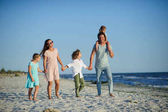 Big happy family walking at the beach. Mom, dad and three children. The blue sky, the sun, fresh sea wind. Pleasure from nature and communication.