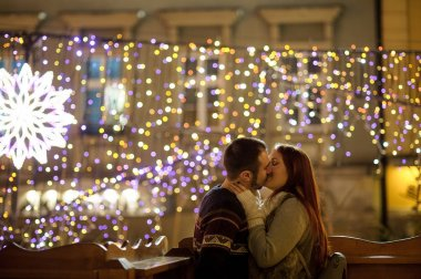 Lovers kiss on the background of shining festive garlands.