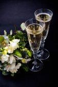 zwei Gläser Champagner und ein Strauß weißer Blumen