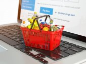 Shopping basket with variety of grocery products ion laptop keyb