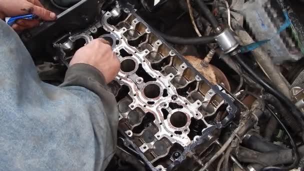 Belső égésű motor javítása. Motorszerelvény. Tömítőanyag alkalmazása egy vezérműtengelyágyon. Tömítőanyag alkalmazása az ujjával.